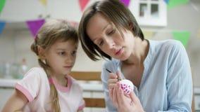 Mutterstudie ihre Tochter, wie man Ei für Feiertag mit einer Bürste zeichnet stock video