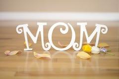 Muttertagbuchstaben mit Blumen und den Blumenblättern stockbild