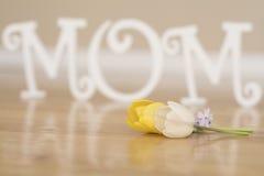 Muttertagbuchstaben mit Tulpenblumen auf Holzfußboden Stockbilder