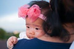 Muttertagesabbindenkonzept mit neugeborener Babykrankenpflege Mutter hält neugeborenes Baby mit Blumenrosastirnband mit blauem Hi Stockfotografie