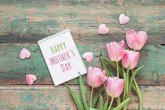 Muttertageshintergrund mit rosa Tulpen und Herzen auf grünem grun Stockfotografie