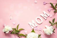 Muttertageshintergrund mit weißen Pfingstrosen und dekorativen Herzen Stockfoto