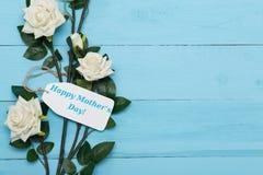 Muttertageskarte und schöne Rosen auf blauem hölzernem Hintergrund Stockfotografie