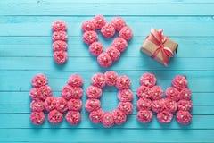 Muttertagesmitteilung von rosa Papierblumen über blauem hölzernem Brett Lizenzfreie Stockfotografie
