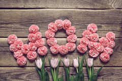 Muttertagesmitteilung von rosa Papierblumen und von Tulpen über altem wo Stockbilder