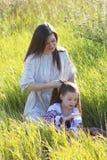 Muttertochter spinnt eine Borte Stockfoto