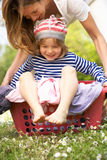 Muttertragender Sohn, der im Wäscherei-Korb sitzt Lizenzfreie Stockbilder