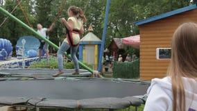 Muttertrieb-Videogebrauch ein Smartphone als Kinder, die auf die Trampoline springen stock video footage