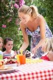 Mutterumhüllung-Geburtstag-Kuchen zur Gruppe Kindern Lizenzfreies Stockfoto