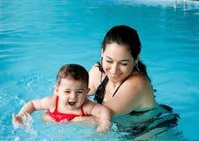 Mutterunterrichtende Schätzchenschwimmen Stockfoto