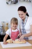 Mutterunterrichtende Tochter, wie man Brot schneidet Lizenzfreie Stockfotografie