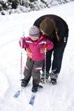 Mutterunterrichtendes Kind zum Ski zu fahren Stockbilder