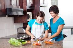 Mutterunterrichtendes Tochterkochen lizenzfreie stockbilder