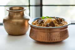 Mutton biryani. Closeup view of delicious mutton (lamb) biryani with mint garnish and served in authentic copper bowl. Natural light used Stock Images