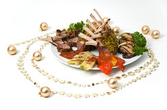 Mutton Chops Decorated. Mutton chops on a plate with vegetables, surrounded by Christmas decorations stock photos