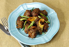 Mutton fry. On a plate on a burlap background stock photos
