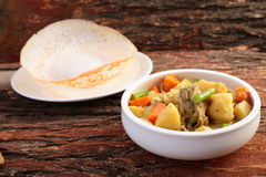 Mutton stew with appam. Kerala cuisine-Soft Appam served with hearty mutton stew on a wooden background royalty free stock photos