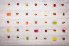 Muttrar, mandlar, hasselnötter och gelégodisar på en ljus träyttersida fodrade med symmetriska rader Härlig bakgrund av godisen Royaltyfria Foton