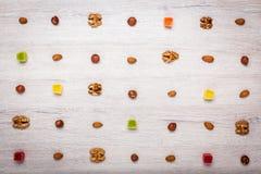 Muttrar, mandlar, hasselnötter och gelégodisar på en ljus träyttersida fodrade med symmetriska rader Härlig bakgrund av godisen Arkivfoto