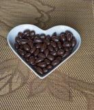 Muttrar ordnade i hjärtaform på bakgrund Matbildslutet upp godisen, choklad mjölkar, extra mörka mandelmuttrar Förälskelsetextur arkivbilder