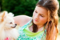 Mutual Admiration. Preteen and her Pomeranian puppy admiring each other stock photos