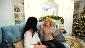 Mutual communication and sharing secrets of two girlfriends who sit on couch in bright living room with festive. Blonde talking on cell with lover and arranges stock video footage