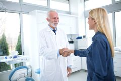 A mutual satisfaction after a successful treatment. Dentist and patient are shaking hands Royalty Free Stock Photo