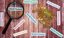 Mutuo ipotecario, lente d'ingrandimento e monete Fotografie Stock Libere da Diritti