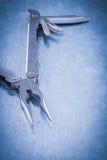 Muunctional roestvrij knipmes op gekraste metaalachtergrond Royalty-vrije Stock Fotografie