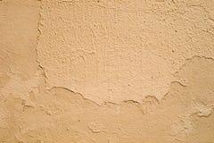 Muur met barsten in het gele pleister stock foto's