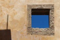 Muur met een venster en een blauwe hemel stock fotografie