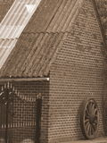 Muur met oud wiel in sepia Stock Foto's