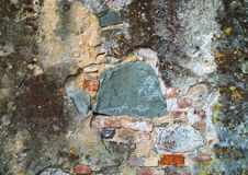 Muur met pleister en versleten door tijd en verwaarlozing is gebarsten die stock fotografie