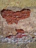 muur met rode baksteen zichtbaar door barsten stock foto's