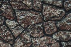 Muur met zwarte en bruine decoratieve geribbelde steen wordt gevoerd die De muur dichte omhooggaand van de steen Rome - Itali? Le stock foto