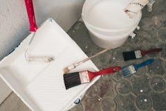 Muur op het schilderen wordt voorbereid die Borstels, emmers van verf, treden dichtbij de muur Stock Fotografie
