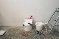 Muur op het schilderen wordt voorbereid die Borstels, emmers van verf, treden dichtbij de muur Stock Afbeeldingen