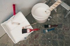Muur op het schilderen wordt voorbereid die Borstels, emmers van verf, treden dichtbij de muur Royalty-vrije Stock Foto