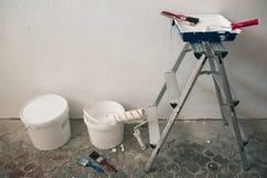 Muur op het schilderen wordt voorbereid die Borstels, emmers van verf, treden dichtbij de muur Stock Foto