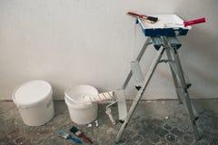 Muur op het schilderen wordt voorbereid die Borstels, emmers van verf, treden dichtbij de muur Stock Foto's