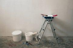 Muur op het schilderen wordt voorbereid die Borstels, emmers van verf, treden dichtbij de muur Royalty-vrije Stock Foto's