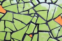 Muur van ceramische stukken groene en oranje kleur voor achtergrond Stock Foto