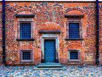 muur van de oude rode baksteen met donkere deur en symmetrische vensters Royalty-vrije Stock Foto's