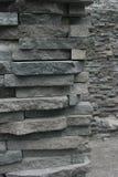 Muur van gelaagde stenen in een onbehouwen patroon met muur op achtergrond die diepte en omvang van de muur tonen stock afbeelding