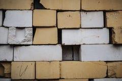 Muur van gele bakstenen een pak verschillende bakstenen royalty-vrije stock afbeeldingen