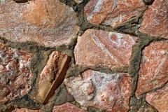 Muur van grote roze rotsen in concrete fototextuur die wordt gemaakt Royalty-vrije Stock Afbeeldingen