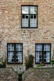 Muur van huis van rode baksteen met drie vensters Stock Fotografie