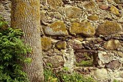 Muur van natuursteen met een klein venster wordt gemaakt dat Stock Afbeeldingen