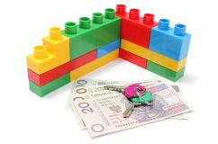 Muur van plastic kleurrijke bouwstenen met huissleutels en geld Stock Afbeeldingen