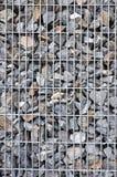 Muur van stenen in een netto staal stock afbeelding